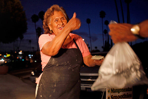 Clarita Trujillo greets a customer with a smile as she hands him his order of food. <br>