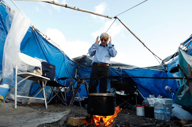 Gennadiy Petrovich Tomashov, 57, prepares soup over an open fire. Tomashov, a homeless truck driver, has been living in tent city for the last eight months.