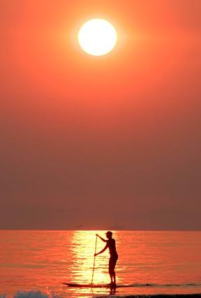 A paddleboarder glides across the water Thursday in Newport Beach as the sun sets in a smoke-filled sky. The winds that fanned the Southern California fires also pushed its smoke far out to sea.