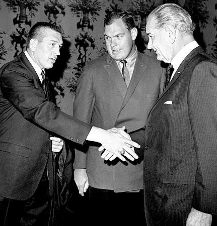 Johnny Unitas, Baltimore Colts quarterback, shakes hands with President Lyndon Johnson as he and Merlin Olsen, center, arrive at the annual Presidential Prayer Breakfast in Washington. Unitas and Olsen  came to Washington with other football stars to plan ways to help inner-city youths.