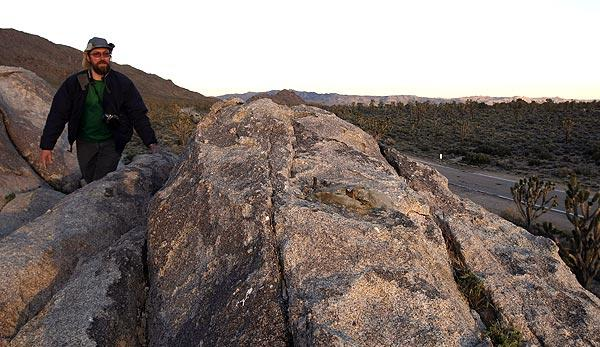 Ken Layne of Yucca Valley climbs to the spot in the Mojave National Preserve where a cross honoring troops who died in World War I vanished. <br>