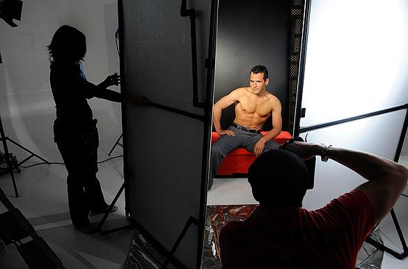 Makeup artist Justina Brittain, left, model Brandon Romain, center, and photographer Shane O'Neal, right, work in a Las Vegas studio during a photo shoot for a controversial calendar of Mormon missionaries. Chad Hardy, an entrepreneur and lapsed Mormon, has created a stir with his hunky calendar.