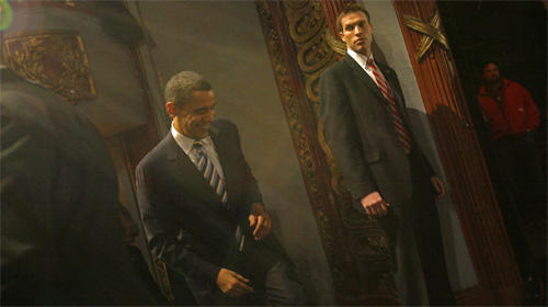 A Secret Service agent, right, watches over Sen. Barack Obama as he leaves the Palace Theater in Manchester, N.H., after delivering a speech Sunday morning.