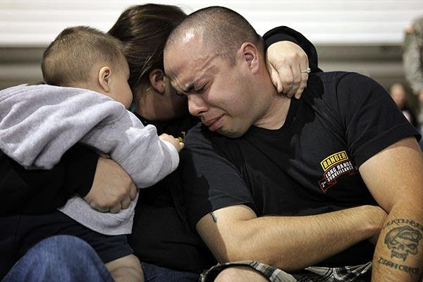Sheldon and Nancy Rabago hold their son, Owen, as they cry during the candlelight vigil at Ft. Hood Stadium in Texas.