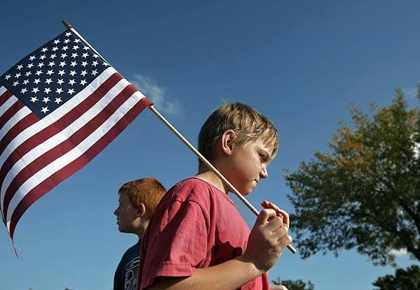 Brothers Valiant, left, and Jeremiah Thomas, 9 and 7, take part in a demonstration of support at the gate of Ft. Hood.