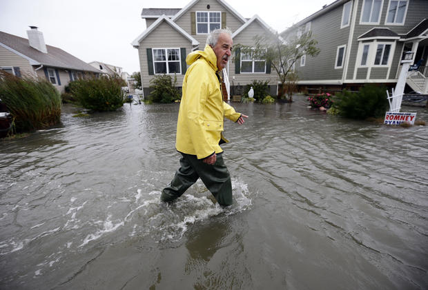 Richard Thomas walks through the flood waters in front of his home after assisting neighbors as Hurricane Sandy bears down on the East Coast in Fenwick Island, Del.