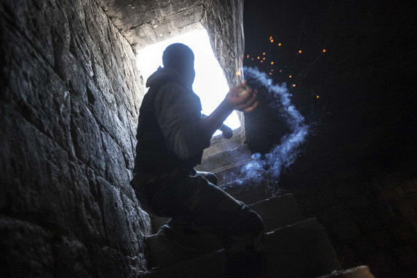 A rebel fighter prepares to throw a homemade grenade toward Syrian troops loyal to President Bashar Assad.