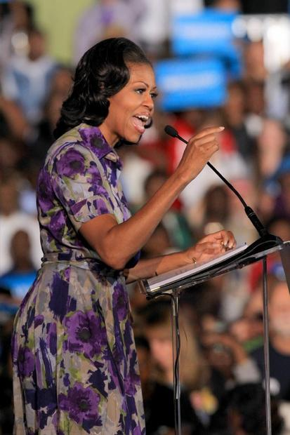 Michelle Obama, in a vibrant purple print with dressmaker details like the buttoned cuffs on the short sleeves, comes across as confident of herself. Here she speaks to a packed house at the Ocean Center in Daytona Beach, Fla.
