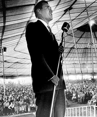 At a revival gathering in Downey, Oral Roberts addresses a packed tent.