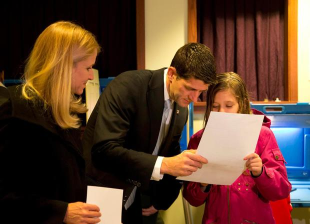 Then-vice presidential candidate Paul Ryan shows his ballot to daughter, Liza, after voting with his family in Janesville, Wisc.