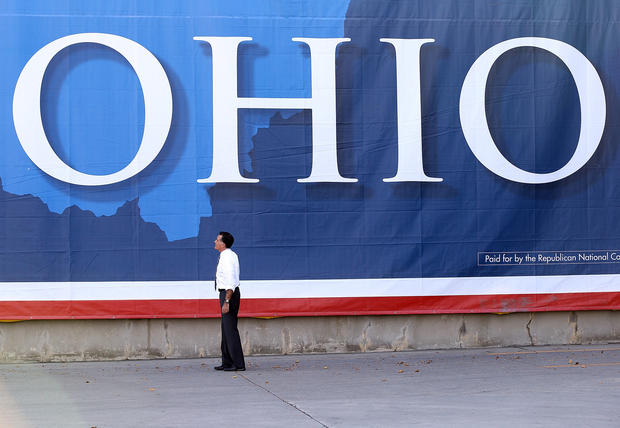 Mitt Romney looks at a large banner during a campaign rally at Worthington Industries in Cincinnati.