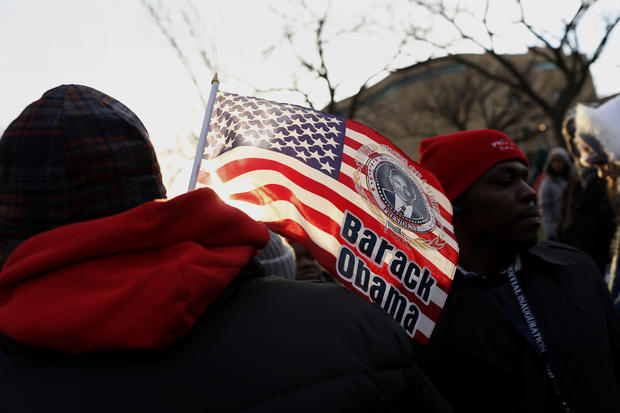 An attendee holds an American flag with an image of President Obama before the start of the presidential inauguration in Washington.