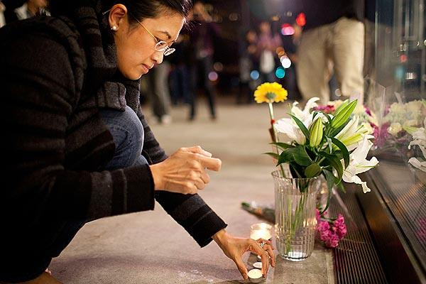 Surina Shukri lights a candle in remembrance of Steve Jobs outside an Apple Store in New York.