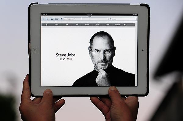The Apple website's home page, paying homage to Steve Jobs, is displayed on an iPad 2.