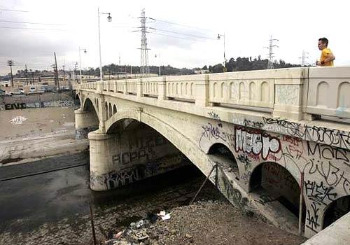 <b>URBAN EYESORE: </b>A jogger crosses the heavily tagged Main Street bridge over the Los Angeles River. The plan envisions widening the channel in places to preserve its flood-control capacity while creating more riparian habitat.