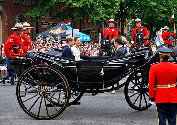 Prince William and wife Catherine, Duchess of Cambridge, left, ride in a landau with Prince Edward Island Premier Robert Ghiz and his wife Kate Ellis Ghiz in Charlottetown.