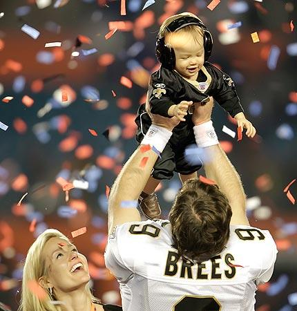 New Orleans Saints quarterback Drew Brees raises his son Baylen in the confetti-filled air as his wife, Brittany, watches after the Saints beat the Indianapolis Colts in Super Bowl XLIV at Sun Life Stadium in Miami Gardens, Fla.