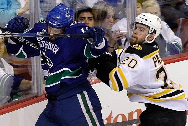 Boston forward Daniel Paille, right, checks Vancouver forward Maxim Lapierre during the first period of Game 7 of the Stanley Cup finals on Wednesday.
