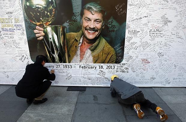 Fans write condolence messages on banners before a memorial service for Lakers owner Jerry Buss at the Nokia Theatre.