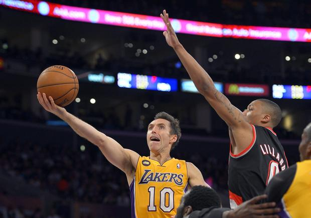 Steve Nash drives past Damian Lillard during the first half of the Lakers' matchup with the Portland Trail Blazers on Friday.