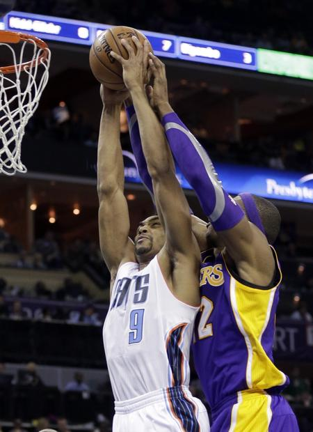 Gerald Henderson goes in for a dunk as Dwight Howard defends during the first half of the Lakers' matchup with the Charlotte Bobcats on Friday.