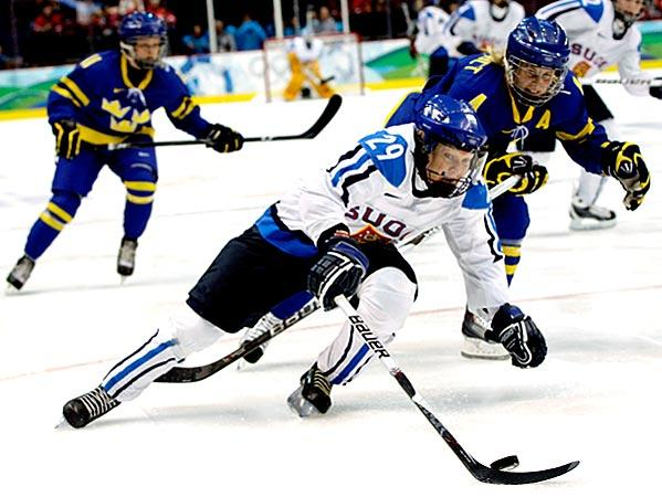 Finland's Karoliina Rantamaki (29) moves the puck ahead of Sweden's Jenni Asserholt (4) in the first period of the women's bronze medal ice hockey game at the Vancouver 2010 Olympics in Vancouver.