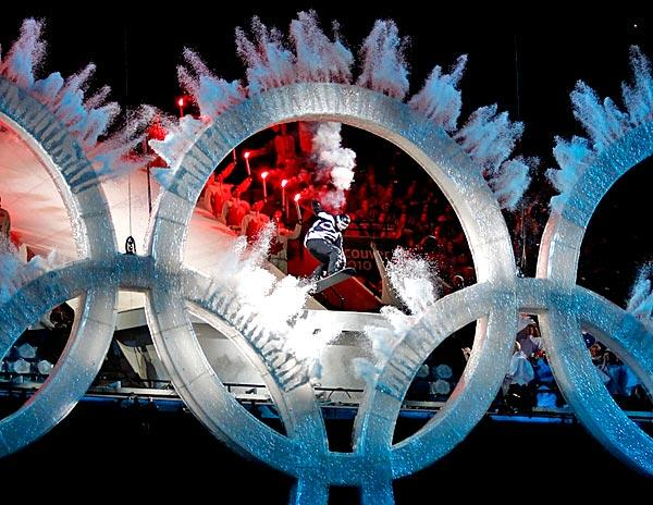 A snowboarder sails through the Olympic rings during the opening ceremony for the 2010 Winter Olympics at Vancouver, Canada.