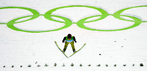 Switzerland's Simon Ammann stretches into the sky en route to winning the gold medal in men's individual ski jumping.