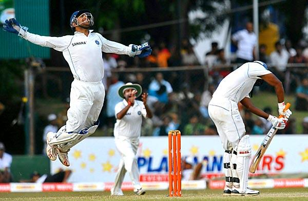Indian cricket captain and wicketkeeper Mahendra Singh Dhoni leaps into the air as he takes a catch to dismiss Sri Lankan batsman Tharanga Paranawethana, right, during the third day of the third test match between Sri Lanka and India at the P. Sara Oval International Cricket Stadium in Colombo. Sri Lanka are 45 runs for the loss of two wickets in their second innings.
