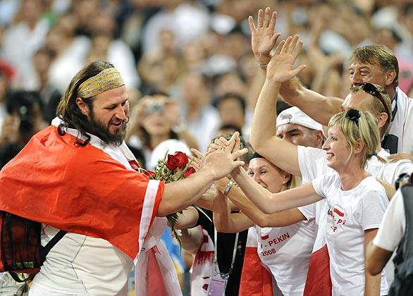 Poland's Tomasz Majewski celebrates with fans after winning the gold medal in the finals of the men's shotput in the 2008 Beijing Olympics.