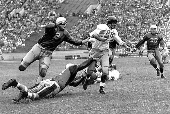 USC halfback Mickey McCardle is brought down by UCLA's Herb Wiener after a five-yard gain during the Sept. 25, 1943, game. The programs would schedule two games for the 1943, '44 and '45 seasons because of travel restrictions during World War II. USC would win nine of the 13 games played in the '40s, with the fourth tie of the series coming at the start of '44.