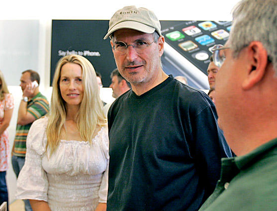 Jobs and his wife, Laurene Powell, meet with customers after the launch of the iPhone.