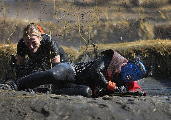 "Tough Mudder competitor David Duong, right, of Los Angeles, lets out a yell as he falls in the mud after being shocked in the ""electroshock therapy"" course."