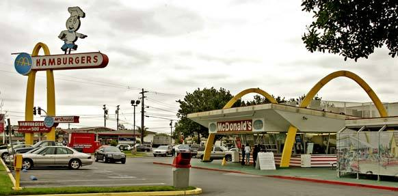 The sign outside the McDonald's restaurant on Lakewood Boulevard in Downey features, not Ronald, but Speedee the chef — the fast-food chain's original spokesman as a symbol of fast, efficient service.  This restaurant, the oldest remaining McDonald's, was restored in 1996, but it continues to mix the old with the new.  The employees dress in 1950s-style uniforms, the bright yellow golden arches are still prominent, and Speedee keeps watch over everything from his 60-foot-high perch.