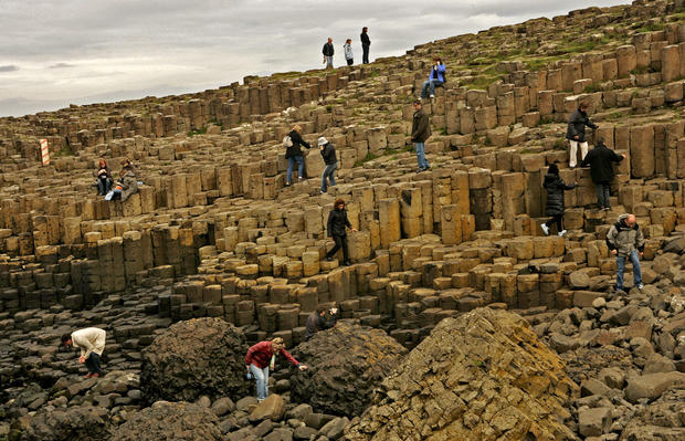 The Giant's Causeway, at the foot of basalt cliffs in Northern Ireland, is made up of 40,000 black basalt columns jutting out of the ocean. Volcanic activity 50 million to 60 million years ago created these step-like columns on the edge of the Antrim plateau.<br>