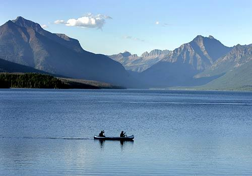 It's a placid day for two canoeists on Glacier Park's Lake McDonald. But along with rugged beauty and wildlife, storms also abound in the area.