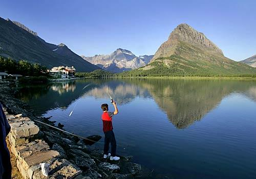 A youthful fisherman flings a line into Swiftcurrent Lake in the park's eastern reaches. He may not hook a fish but he needn't go hungry, for the rustically gracious Many Glacier Hotel is nearby. The proximity of lake and hotel illustrates Glacier's means of satisfying both hardy outdoors enthusiasts and hearty appetites.