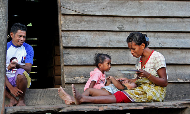 A woman feeds her infant on one of the Maluku Islands.