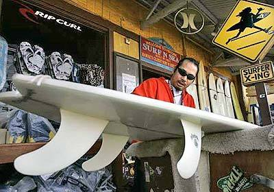 Richard Samiley scrapes the wax off a surfboard being prepared for consignment at the Surf 'N Sea shop in Haleiwa.