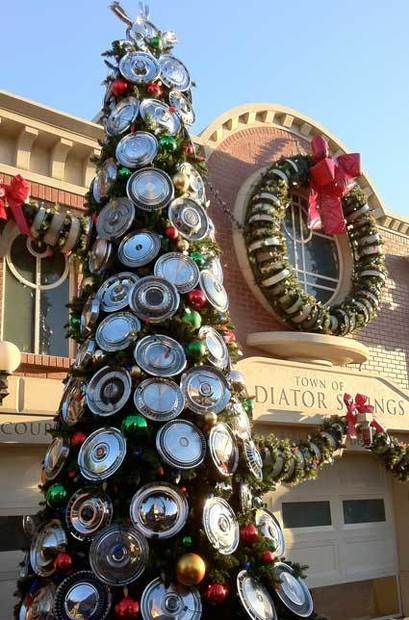 A Christmas tree decorated with 1950s and '60s hubcaps stands in front of the Radiator Springs courthouse in Cars Land at Disney California Adventure.