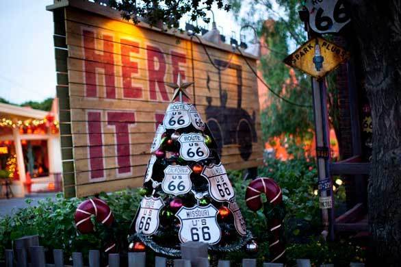 A Christmas tree adorned with Route 66 highway signs stands in front of the Radiator Springs Curios gift shop in Cars Land at Disney California Adventure.