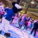 Passengers wait in line to pose with Mickey Mouse in the atrium of the Disney Dream cruise ship.