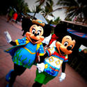 Minnie and Mickey Mouse walk hand-in-hand around Castaway Cay, a stop on the Disney Dream cruise.