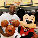 Miami Heat basketball star Dwayne Wade shoots hoops with a sporty Mickey Mouse.