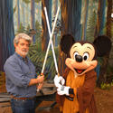 """Star Wars"" creator George Lucas squares off for a lightsaber battle with Jedi Mickey."
