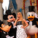 Singer Jessica Simpson gets an escort from a tuxedo-wearing Mickey Mouse, Goofy and Donald Duck at the Magic Kingdom.