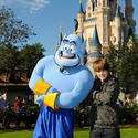 Injured pop singer Justin Bieber (with a busted foot) strikes a pose with Aladdin at the Magic Kingdom.