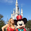Singer Mariah Carey in her Christmas best with a top hat-wearing Mickey Mouse at the Magic Kingdom.