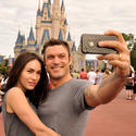 """Transformer"" star Megan Fox and actor-husband Brian Austin Green snap a self-portrait with their cell phone camera in front of Cinderella Castle at the Magic Kingdom.."