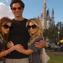 "Mary-Kate and Ashley Olsen hug former ""Full House"" co-star John Stamos in front of the Cinderella Castle at the Magic Kingdom."